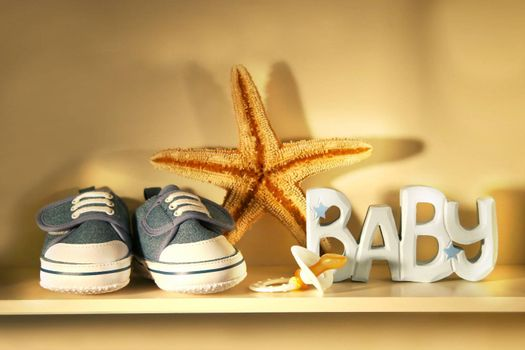 Baby shoes place on a shelf with baby pacifier, starfish etc..