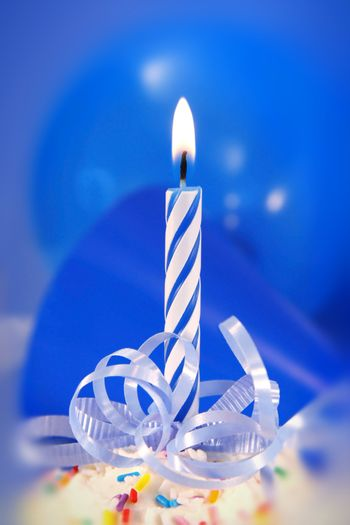 Small blue candle with ribbons ready for a birthday