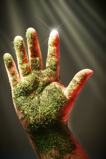 Open hand with green substance against dark background