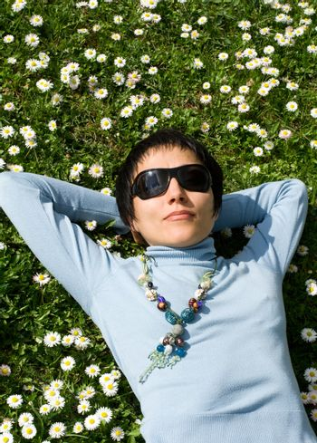 Young woman is dreaming on the flowering meadow
