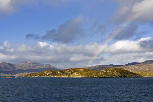 coastal scene in scotland with rainbow over hills