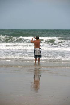 man shooting the waves on white sand beach koh chang island thailand