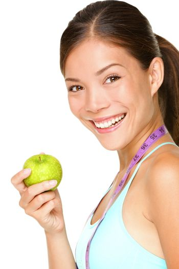 Healthy lifestyle. Fitness woman eating apple wearing measuring tape. Fit sporty multicultural Asian / Caucasian female fitness woman isolated on white background.