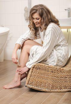 Woman depilating her leg