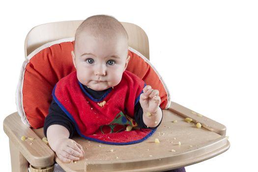 toddler eating potatoes in highchair