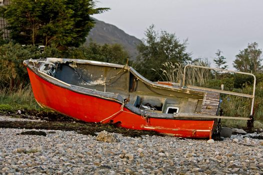 read boat at coast in scotland with trees in background