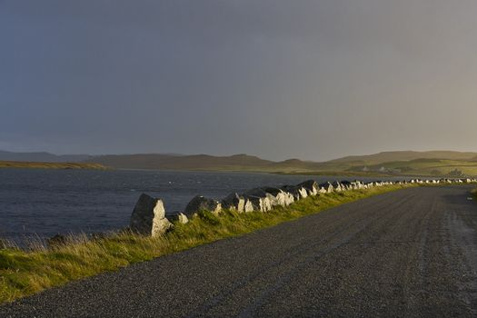 lonely road at loch in scotland in evening light