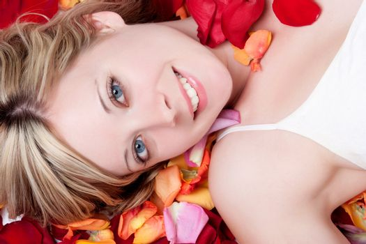Smiling woman in rose petals