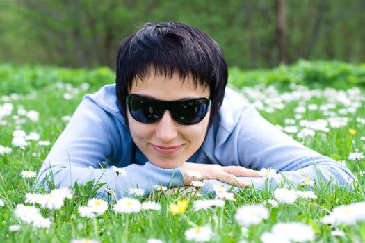 Young woman in sunglasses is lying on the flowering meadow