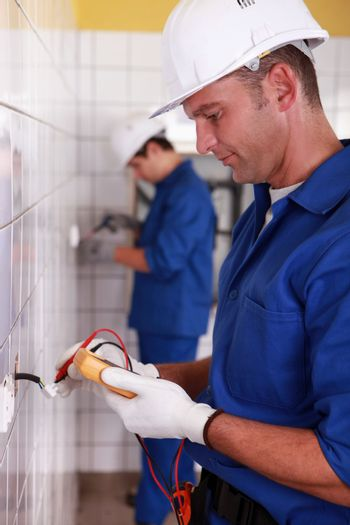 Electricians installing switches