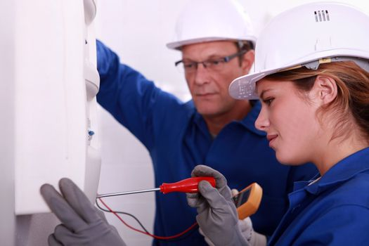 a young woman working on an electricity meter accompanied with a 45 years old man, both are wearing blue jumpsuites