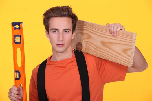 junior carpenter posing with ruler and lumber over shoulder