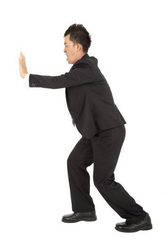 Businessman pushing away the wall