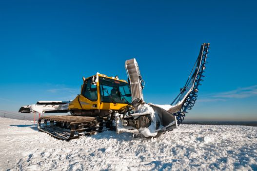 Snowcat for making half pipes, standing on top of the mountain