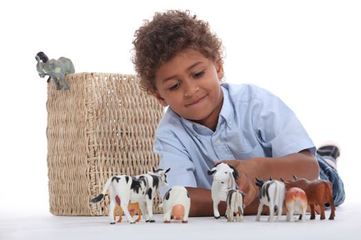 Little boy playing with his toy animals