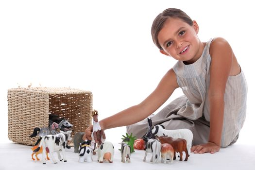 Little girl playing with toy animals