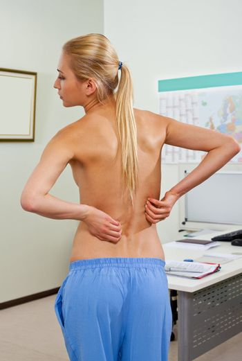 Topless female patient in doctors cabinet, with back pain