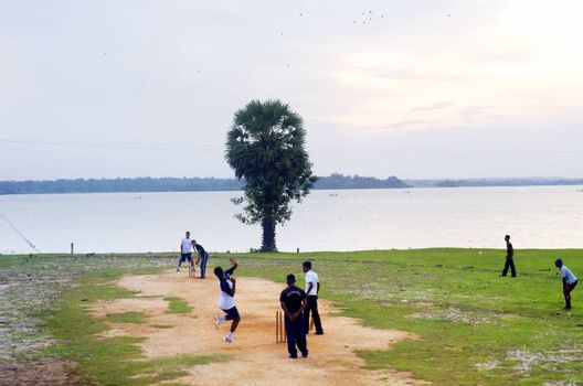 Arugam Bay, Sri Lanka - February 14, 2011: Group of locals are playing cricket. The cricket is the most popular game in Sri Lanka, India and Pakistan. People play it everywhere, yard, street and play ground.