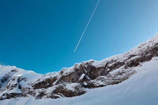 Airplane Trail in Blue Sky above Mountain Peak, French Alps