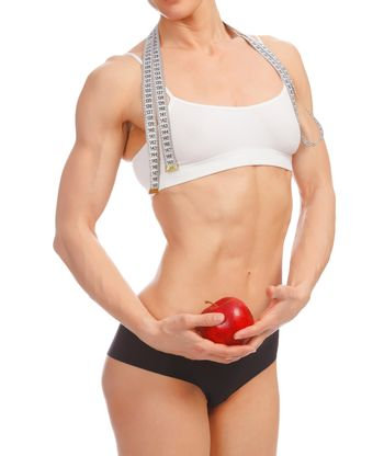 Muscular woman with apple and tape measure