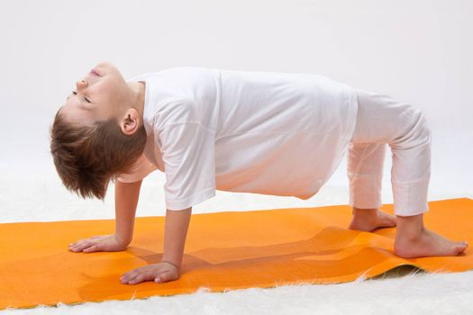 \Children's yoga. The little boy does exercise.