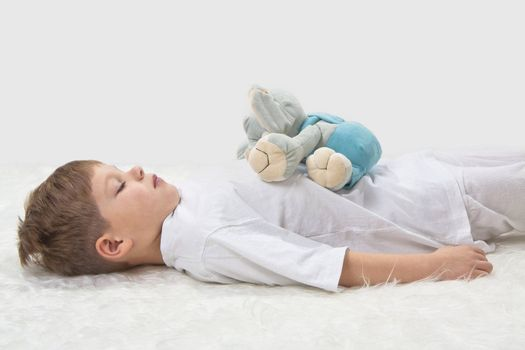 Children's yoga. Yoga before a sleeping. The kid with a favourite toy