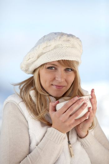 pretty girl drinking tea by wintry day