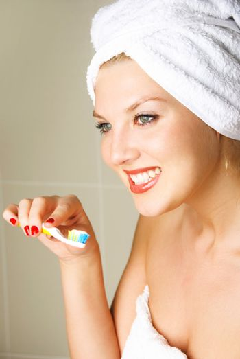 beautiful happy young woman brushing teeth and smiling