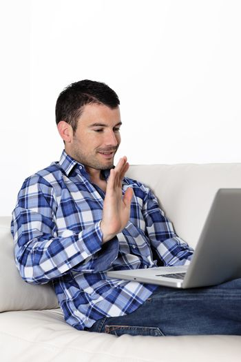 Portrait of a man waving at a laptop