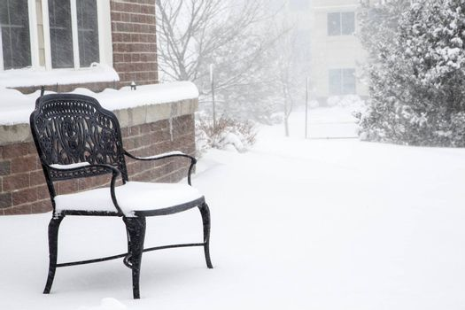 An empty, black, wrought iron bench in a snow storm by a brick building