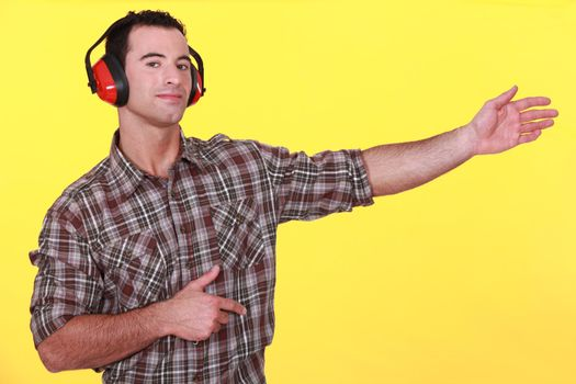 Man wearing earmuffs presenting an invisible object