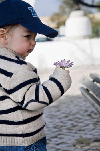 View of a young child holding a flower with a cap.