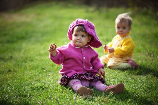 Two baby girls sitting on the grass