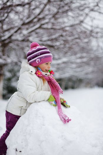 Portrait ov cute little child playing with snow outdoors in winter
