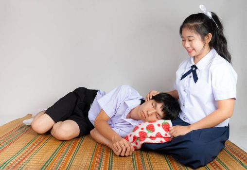 Boyfriend lies down on girlfriend's lap in high school uniform