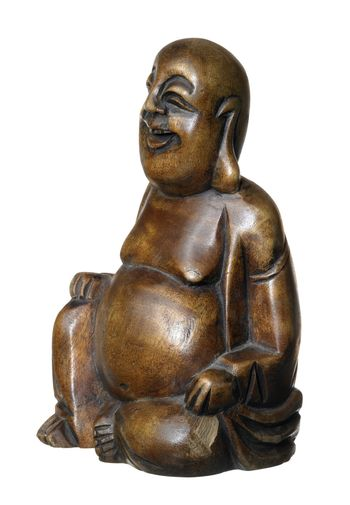 studio photography of a wooden Buddha sculpture in white back