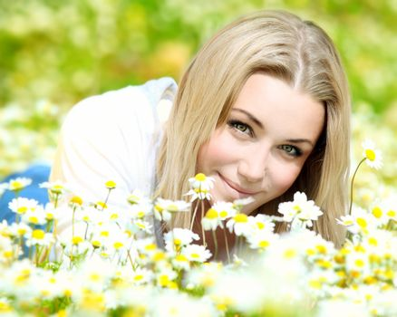 Young beautiful girl laying on the daisy flowers field, outdoor portrait, summer fun and freedom concept