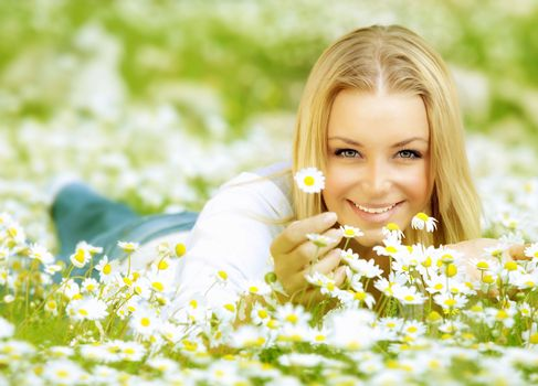 Beautiful woman enjoying daisy field, nice female lying down in the meadow of flowers, pretty girl relaxing outdoor, having fun, hand holds plant, happy young lady and spring green nature, harmony concept