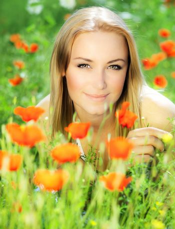 Young beautiful girl enjoying on the poppy flowers field, outdoor portrait, summer fun concept, beautiful woman relaxing in the floral garden, female at fresh spring meadow, people rural leisure