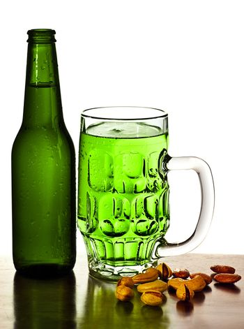Irish green beer, traditional alcohol for st.Patrick's day holiday celebration, lucky clover beverage, glass with nuts, food and drink still life, isolated on white background