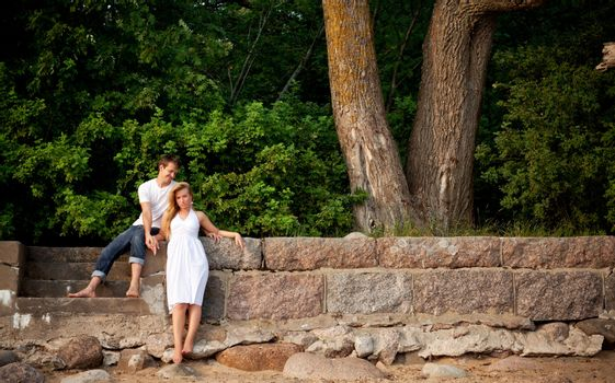 couple stand next stonewall in forest
