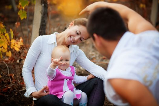 Portrait of loving young parents walking with their baby in autumn park