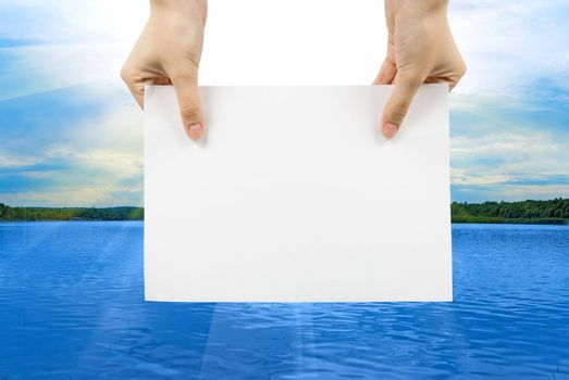 Hand with white paper on a summer lake background