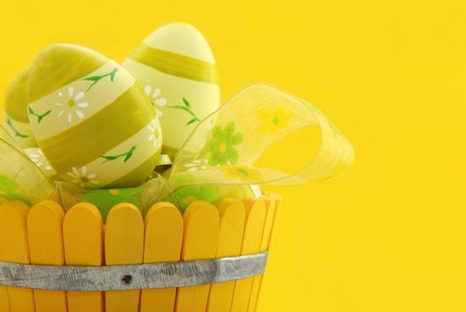 Easter eggs in the basket isolated on yellow background