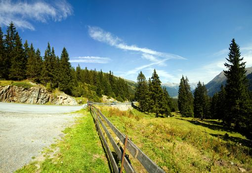 An image of a road in summer forest and mountains