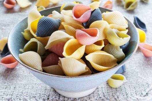 Multi colored pasta in bowl on coarse cloth