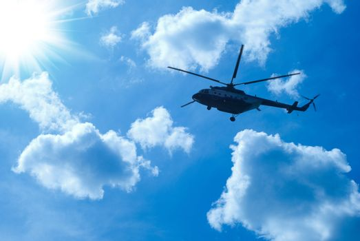 helicopter is flying in blue sunny sky