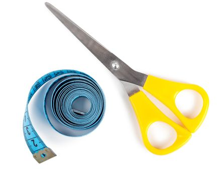 Closeup view of blue measuring tape and scissors over white background