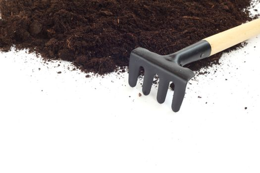 Rake and dirt isolated on white background, gardening concept