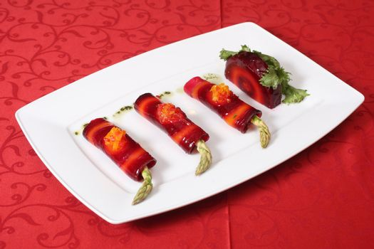 Vegetable rolls with asparagus and red beet on a white plate